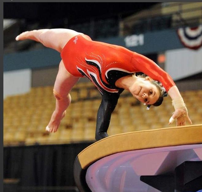 Junior Jill Frasier competes in the vault event at a competition.