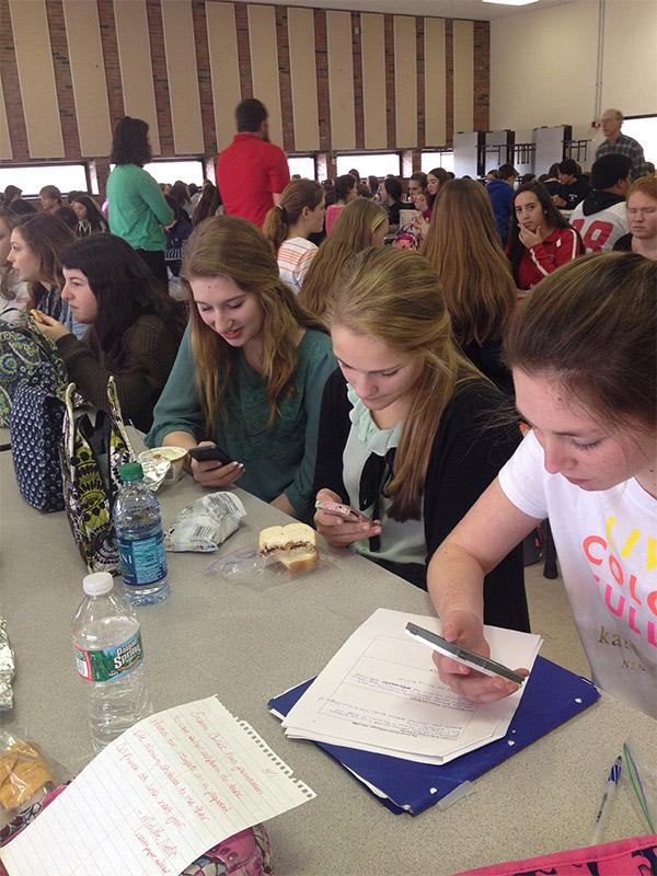 Taylor Parmenter, Kelley Glennon, and Heather Lewis use their phones during lunch block.