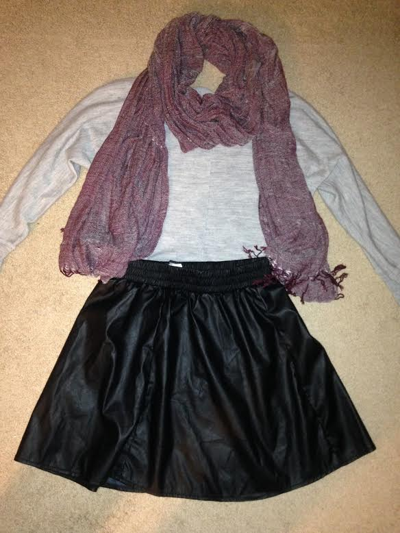 Katie's creation includes a leather skirt, simple grey sweater, and a scarf for a pop of color.