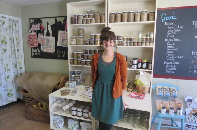 Nicole Cormier of FarmFare Market sits in front of shelves of locally grown herbs, spices and jams at her store in Sandwich