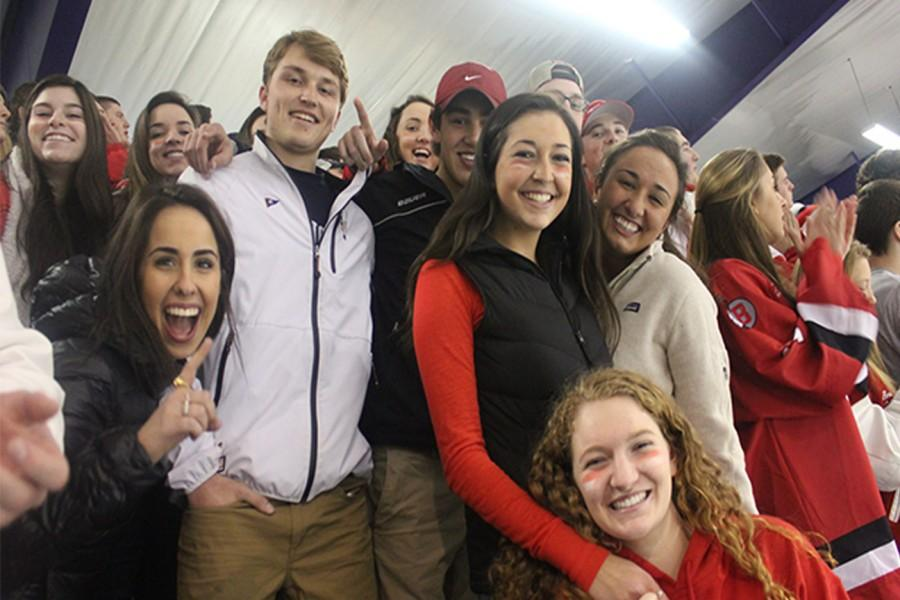 Barnstable fans smile for the camera at a hockey game where the Barnstable Raiders took on the Falmouth Clippers.